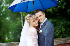 Gelukkige bruid en bruidegom bij huwelijk onder een paraplu Stock Afbeelding