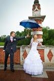Gelukkige bruid en bruidegom bij huwelijk onder een paraplu Royalty-vrije Stock Afbeeldingen