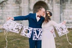 Gelukkige bruid en bruidegom die de artistieke brieven van de papercutliefde openlucht houden Royalty-vrije Stock Fotografie