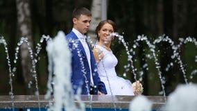 Gelukkige bruid en bruidegom die dichtbij de fontein binnen lopen stock footage