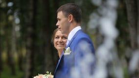 Gelukkige bruid en bruidegom die dichtbij de fontein in het park lopen stock video