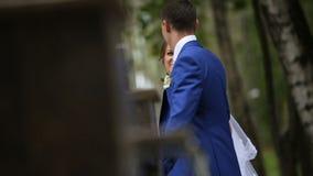 Gelukkige bruid en bruidegom die dichtbij de fontein in het park lopen stock footage