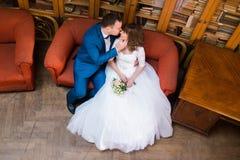 Gelukkige bruid en bruidegom die op rode bank bij oude bibliotheek rusten Stock Fotografie