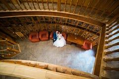 Gelukkige bruid en bruidegom die op rode bank bij oude bibliotheek rusten De mening vanaf de bovenkant Stock Afbeeldingen