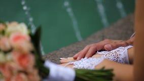 Gelukkige bruid en bruidegom die zich dichtbij de fontein in het park bevinden stock videobeelden