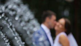 Gelukkige bruid en bruidegom die zich dichtbij de fontein in het park bevinden stock footage