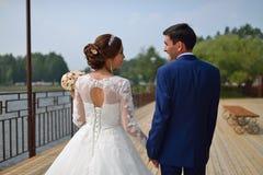 Gelukkige bruid en bruidegom het lopen holdingshanden van rug royalty-vrije stock fotografie