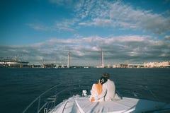 Gelukkige bruid en bruidegom op een jacht die samen reizen Stock Afbeeldingen