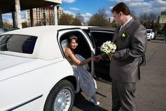Gelukkige bruid en bruidegom uit huwelijkslimousine Royalty-vrije Stock Foto