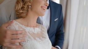 Gelukkige bruid en bruidegomtribune dichtbij het venster stock videobeelden