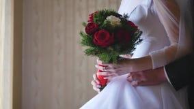 Gelukkige bruid en bruidegomtribune dichtbij het venster Jong aardig het huwelijksboeket van de vrouwengreep in haar handen Het p stock videobeelden