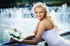 Gelukkige bruid met boeket van bloem dichtbij fontein Royalty-vrije Stock Afbeeldingen