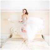 Gelukkige bruid met de donkere sprongen van het blondehaar op het bed Stock Afbeeldingen