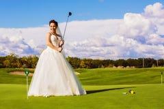 Gelukkige bruid met hout op golfgebied stock fotografie