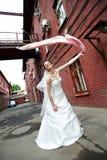 Gelukkige bruid op achtergrond van de oude rode bouw Stock Afbeelding