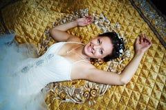 Gelukkige bruid op een luxebed Royalty-vrije Stock Afbeelding