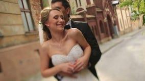 Gelukkige bruidegom die en zijn mooie blondebruid voor een oude christelijke kerk in Lviv spinnen kussen charming stock footage