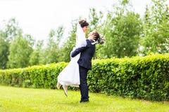 Gelukkige bruidegom die jonge mooie bruid in zijn wapens houden Royalty-vrije Stock Foto's