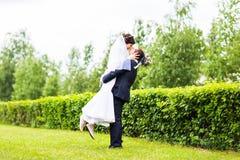 Gelukkige bruidegom die jonge mooie bruid in zijn wapens houden Stock Foto's