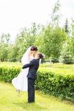 Gelukkige bruidegom die jonge mooie bruid in zijn wapens houden Stock Afbeelding