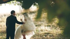 Gelukkige bruidegom die op een schommeling de bruid in het park in de zomer slingeren groepswerk van een paar in liefde jongen en stock footage