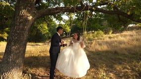 Gelukkige bruidegom die op een schommeling de bruid in het park in de zomer slingeren de jongen en het meisje slingeren op een ta stock videobeelden