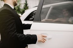 Gelukkige bruidegom die zijn mooie bruid helpen uit de huwelijksauto stock afbeeldingen