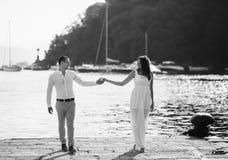 Gelukkige bruidegom en bruid die in witte kleding overzeese achtergrond koesteren Royalty-vrije Stock Afbeelding