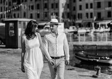 Gelukkige bruidegom en bruid die in witte kleding overzeese achtergrond koesteren Stock Afbeeldingen