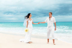 Gelukkige bruidegom en bruid op het zandige tropische strand Huwelijk en h Royalty-vrije Stock Foto