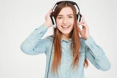 Gelukkige charmante jonge vrouw die in hoofdtelefoons aan muziek luisteren Stock Afbeelding