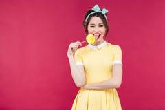Gelukkige charmante jonge vrouw die zoete lolly en het knipogen eten Stock Foto