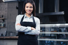 Gelukkige charmante vrouwelijke kelner in schort stock afbeelding