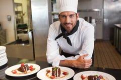 Gelukkige chef-kok die camera achter teller van desserts bekijken royalty-vrije stock afbeelding