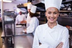 Gelukkige chef-kok die zich in commerciële keuken in een restaurant bevinden stock afbeeldingen