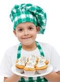 Gelukkige chef-kokjongen met een plaat van muffins stock afbeelding