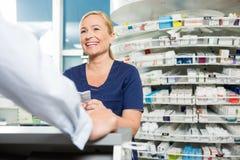 Gelukkige Chemicus Looking At Customer in Apotheek stock foto