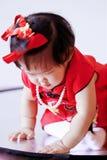 Gelukkige Chinees weinig baby in rode cheongsam heeft pret Stock Afbeeldingen