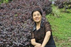 Gelukkige Chinese rijpe vrouw in aard Royalty-vrije Stock Fotografie