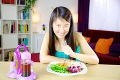 Gelukkige Chinese vrouw die op dieet salade thuis eten stock foto
