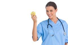 Gelukkige chirurg die een appel houden en bij camera glimlachen Stock Afbeeldingen