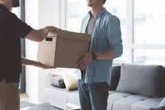 Gelukkige cliënt die pakket van arbeider houden Stock Fotografie