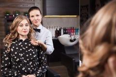 Gelukkige cliënt die spiegel in salon bekijken royalty-vrije stock afbeeldingen