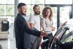 Gelukkige cliënten en autohandelaar die auto waarnemen stock fotografie