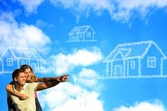 Gelukkige coupleunder de blauwe hemel die van een huis dromen. Stock Afbeelding