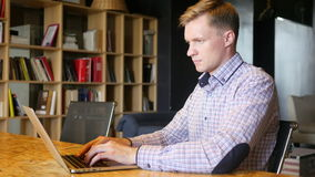 Gelukkige creatieve jonge mens die met laptop bij bureau in zijn bureau werken, stock videobeelden