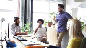 Gelukkige creatieve team het drinken koffie in bureau stock video