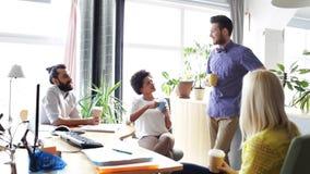 Gelukkige creatieve team het drinken koffie in bureau stock videobeelden