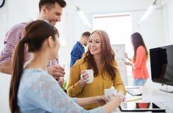 Gelukkige creatieve team het drinken koffie op kantoor royalty-vrije stock foto's