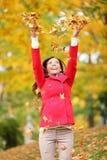 Gelukkige dalingsvrouw die bladeren werpt Royalty-vrije Stock Foto